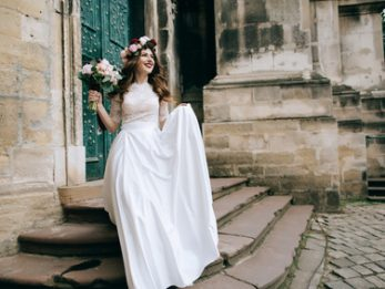 Beautiful bride portrait outdoors on the steps of the church in old city. Wedding concept