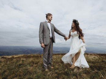 beautiful stylish groom holding fabulous happy emotional bride and having fun on the background of the sunny stunning mountains