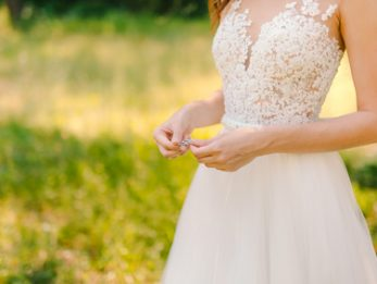 Earrings in the hands of the bride. Wedding in the forest.