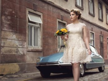Beautiful young bride posing in a wedding dress in a retro cobble street, with an old timer car in the background, holding a sunflower bouquet