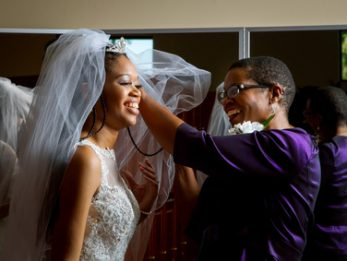 Mother of the bride adjusts her daughter's veil on her wedding day.  Beautiful, African American women, smiling while getting the daughter ready for her wedding.