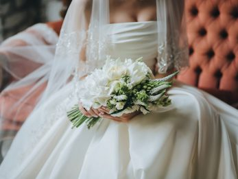 bride in a white dress sitting on a vintage couch in the loft and holding a bouquet of flowers and greenery