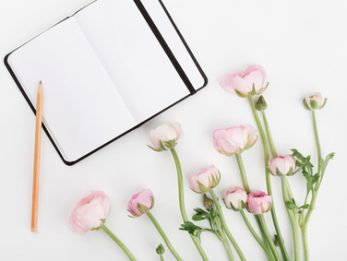Beautiful spring Ranunculus flowers and empty notebook on white table from above. Mockup. Pastel color. Clean space for text. Flat lay style.