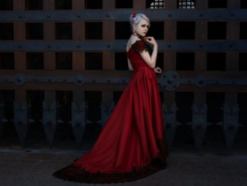 Woman in a long red dress, she is near the gate of an ancient castle.