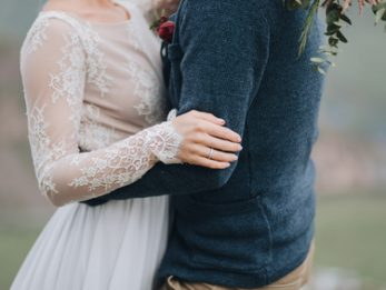 Wedding. mountains. bride's bouquet. Artwork. Grain. Guy hugs a girl in a dress on a background of mountains, a girl holding a bouquet of red flowers, white flowers and greenery